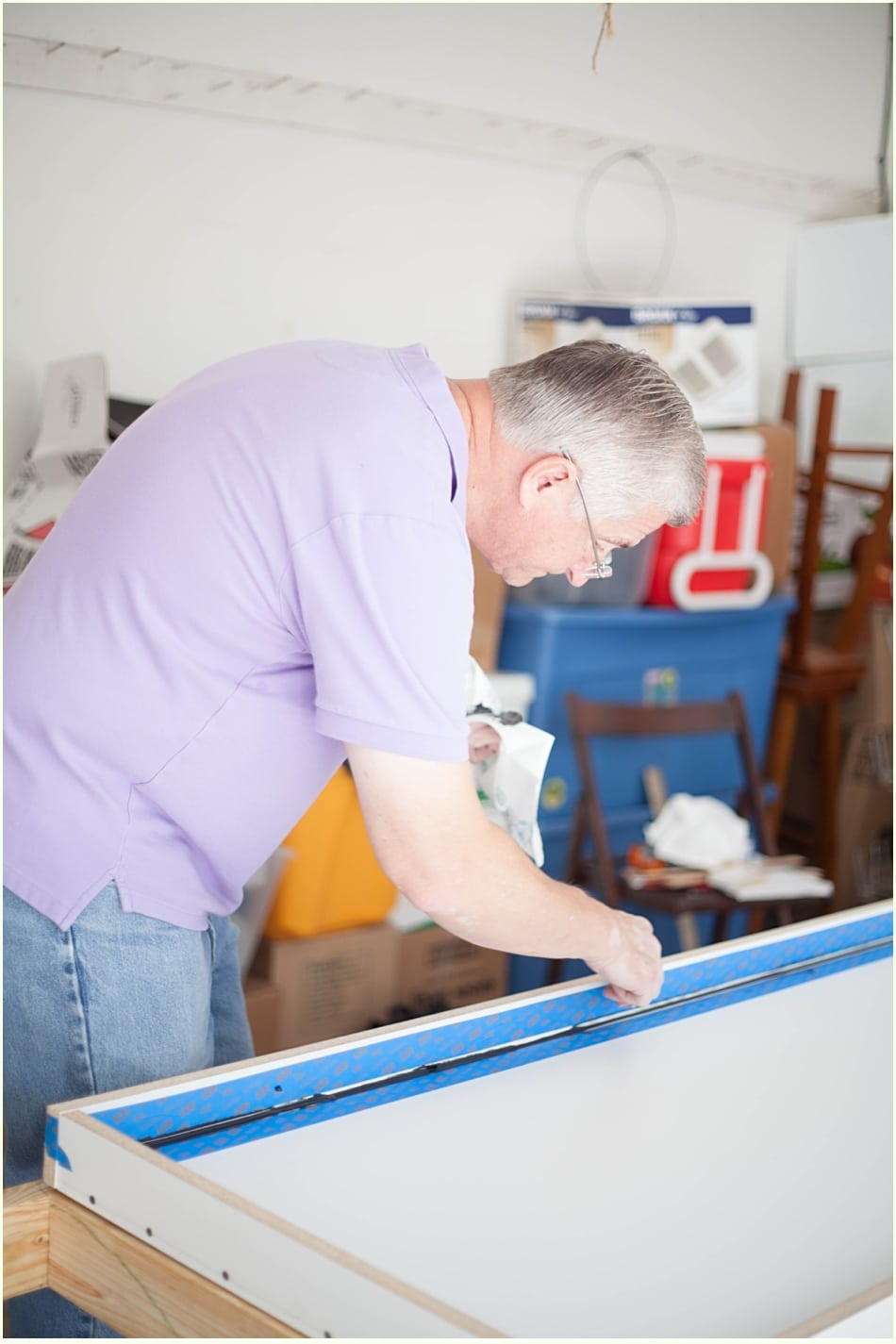 Applying painter's tape to the edge of a countertop mold.