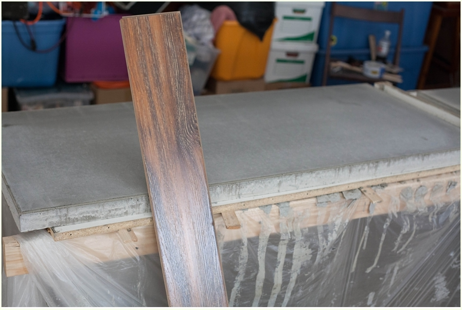 A plank of wood flooring next to a finished concrete countertop slab.