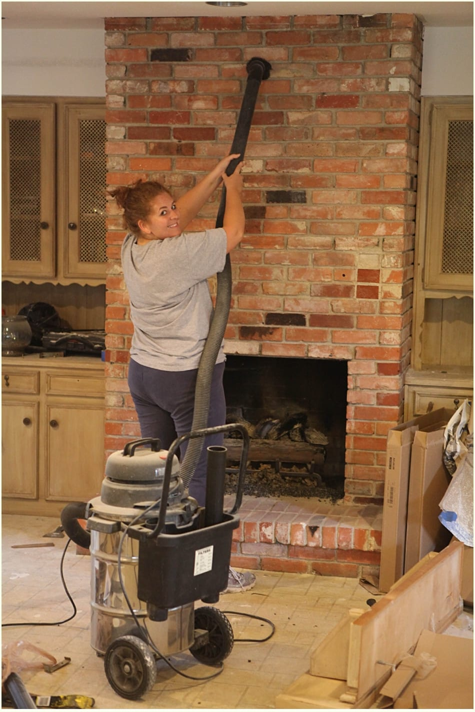 Using a vacuum to clean a fireplace before a whitewash brick project.