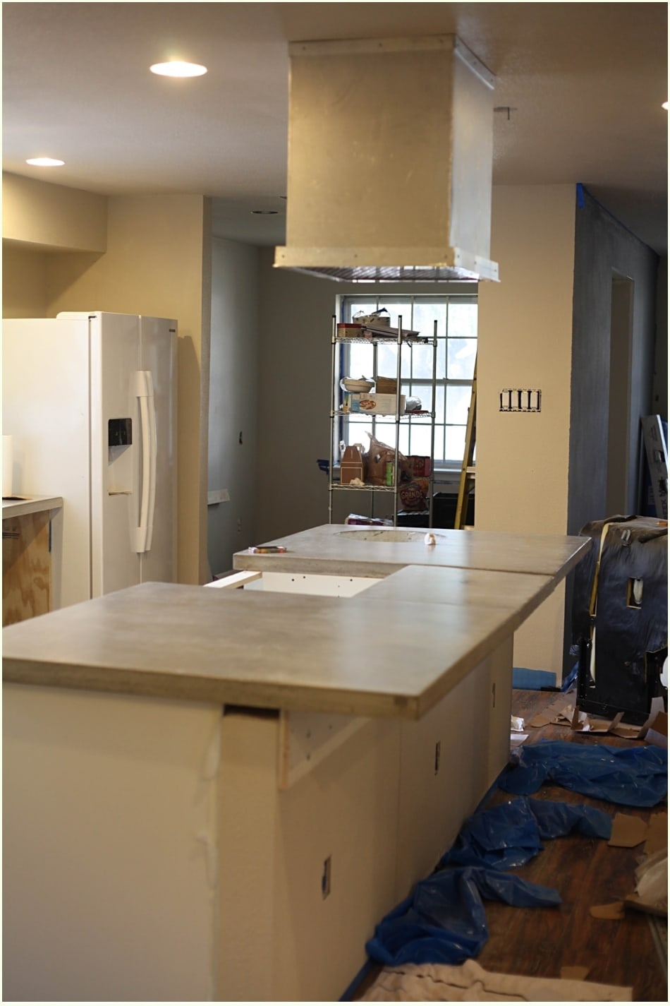 A kitchen with smooth cement slabs as countertops, with cabinets still under construction.
