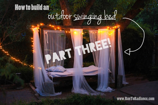 Hanging bed outdoors at night with mosquito netting and twinkle lights