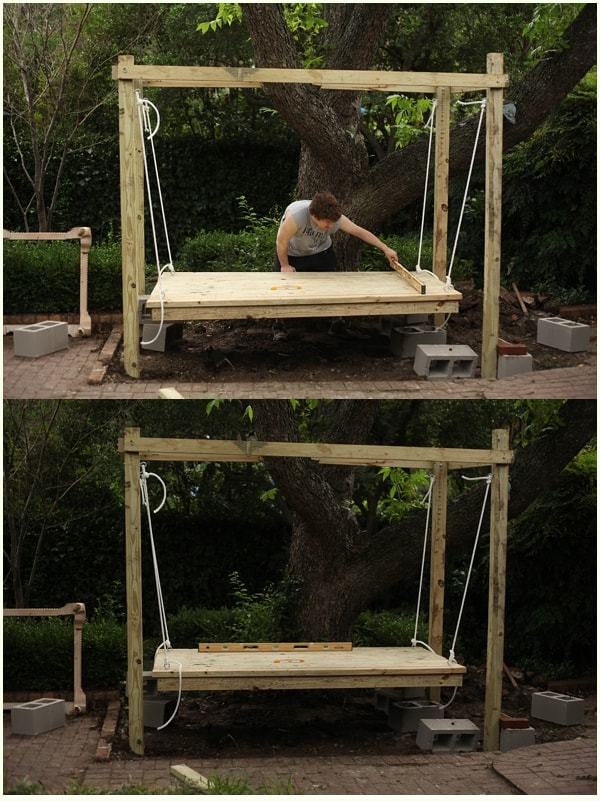 Man checking to make sure an outdoor swing bed is level