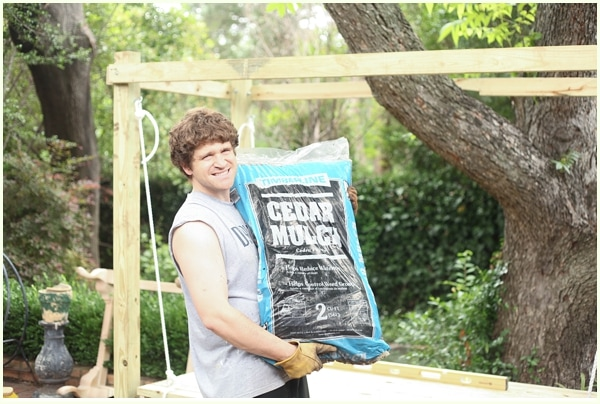 Man carrying a large bag of cedar mulch with outdoor swing bed in background