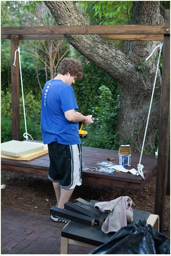 Man with drill hanging curtains around a hanging bed outdoors