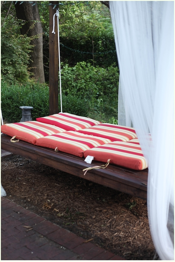 Outdoor swing bed with red striped cushions and mosquito netting