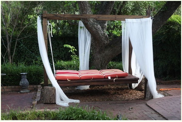 Hanging bed under a tree outside with red stripped cushions and mosquito netting