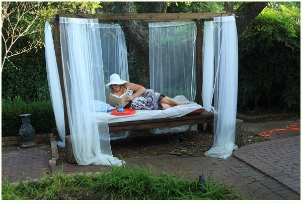 Woman in a sunhat reading a book in a hanging bed outdoors
