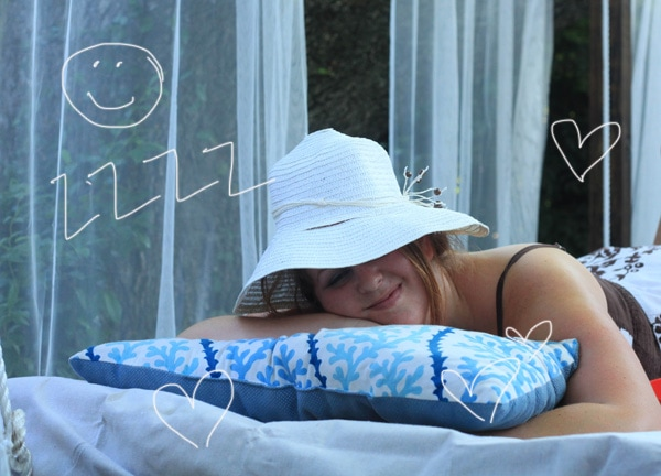 Woman napping in a sun hat on an outdoor swing bed