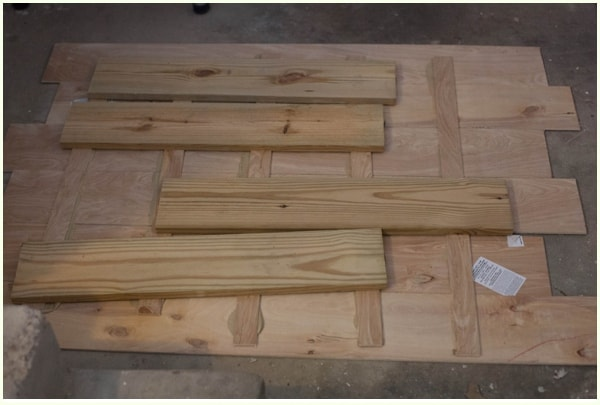 Wooden beams laid on top of plywood to make DIY halloween decor sign.