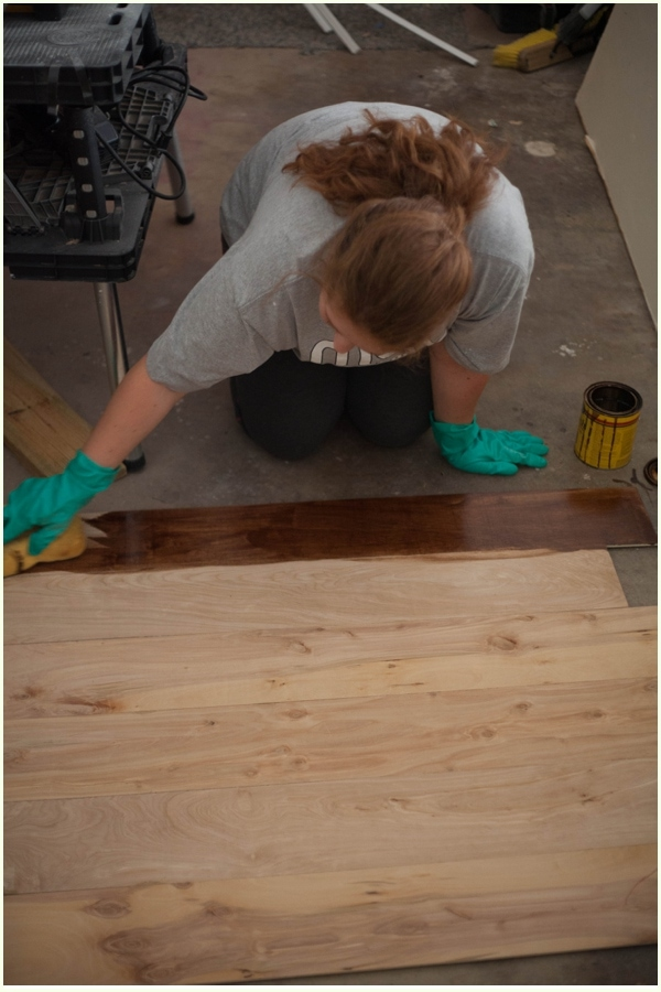 Minwax wood stain in Honey color being applied to raw wood with a sponge.