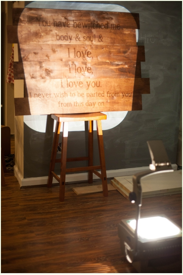 An overhead projection of a romantic book quote on wooden canvas.