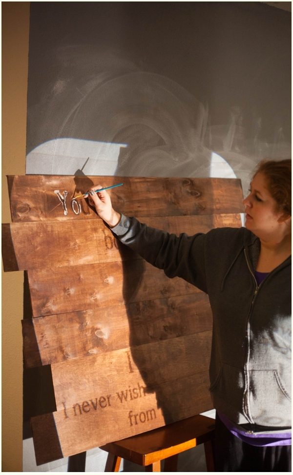 A small paint brush with white chalk paint being used to outline the letters projected onto DIY halloween decor for your home.