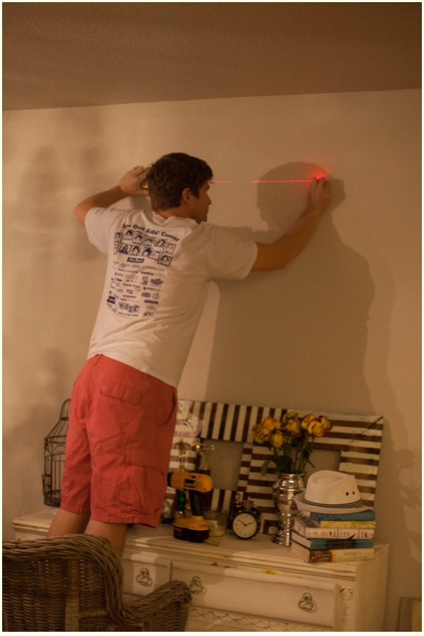 A man standing in a chair to mount wooden halloween decor to wall, checking the area with a level.