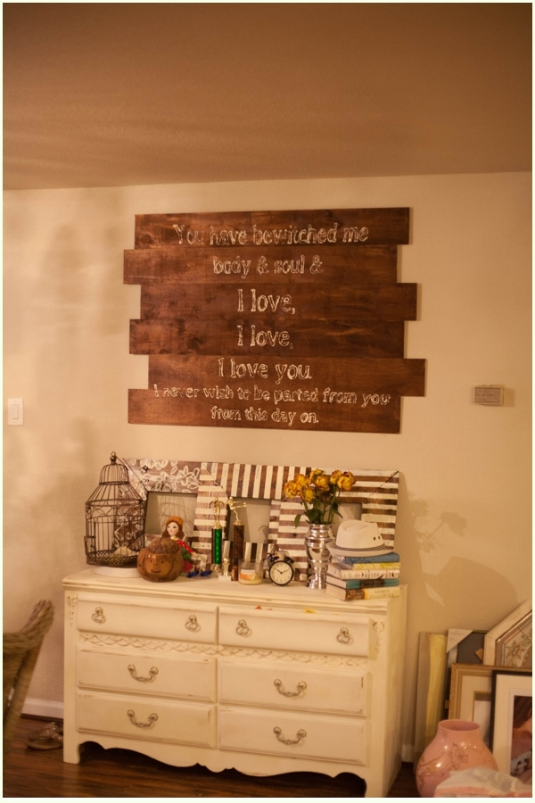 A wooden canvas featuring a romantic halloween quote, hung on a wall above a white painted dresser.