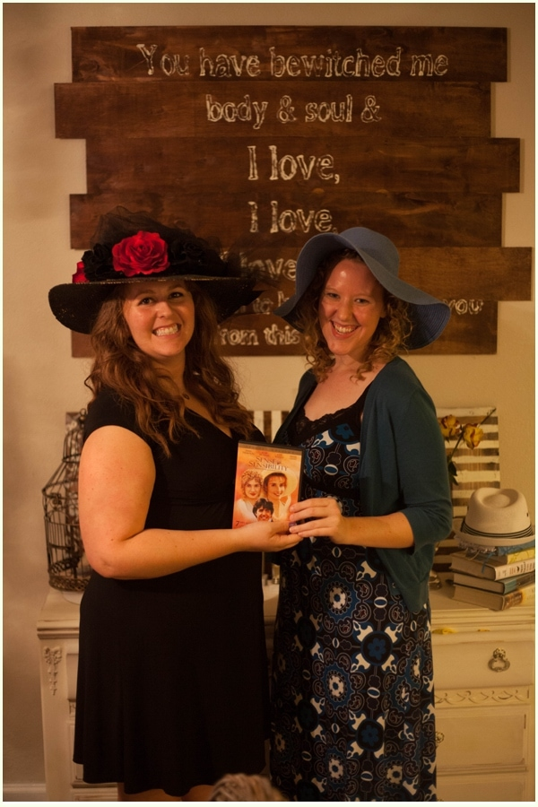 Two women with fancy hats holding a movie on DVD, standing in front of DIY decor project for halloween.