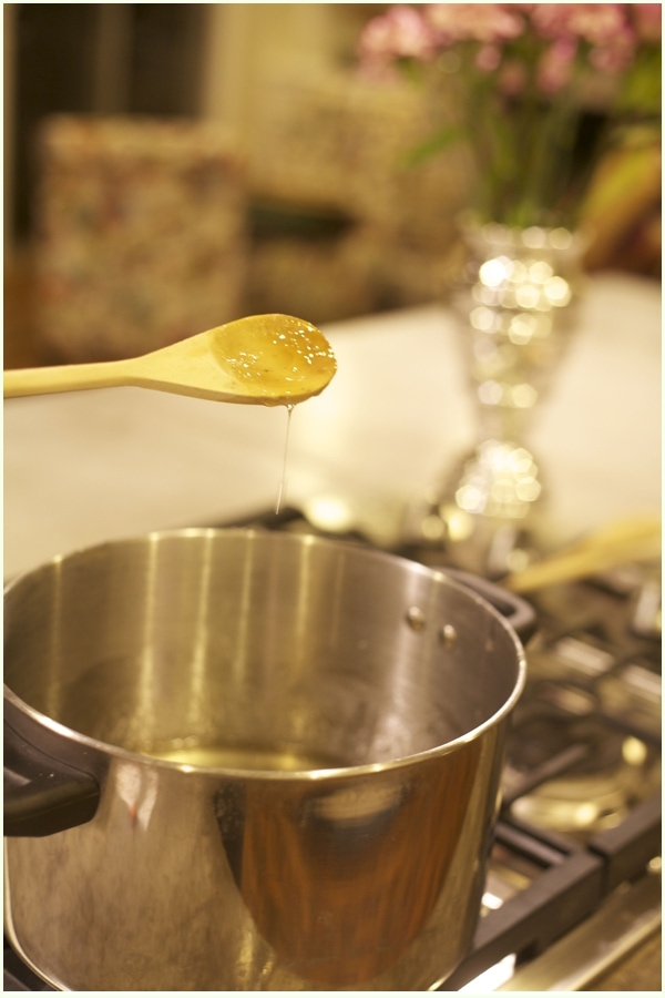 wooden spoon with strings of peppermint syrup dripping- Steps for making peppermint vodka