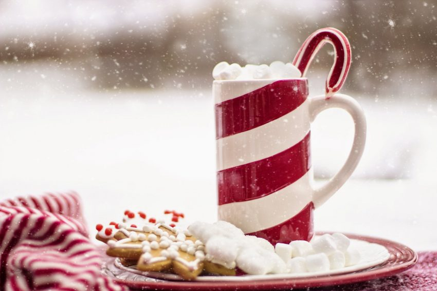 A red and white striped mug with marshmallows and a candy cane sticking out the top, on a plate of cookies with falling snow in the background.