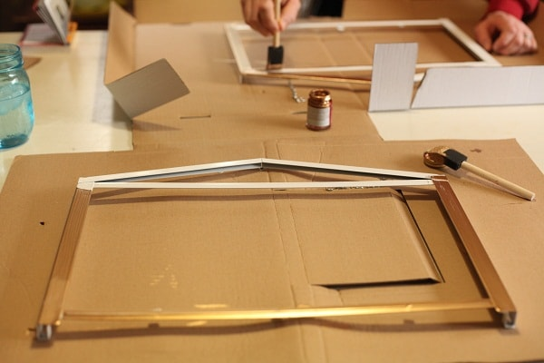 A white greenhouse frame being painted with gold gilding.