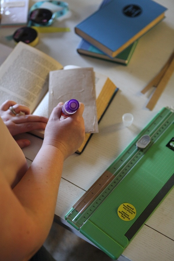 Applying glue to craft paper pages for DIY journal out of an old book
