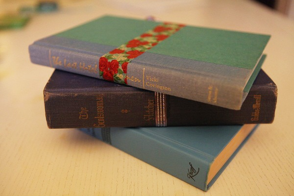 A stack of vintage chapter books, one embellished with washi tape.