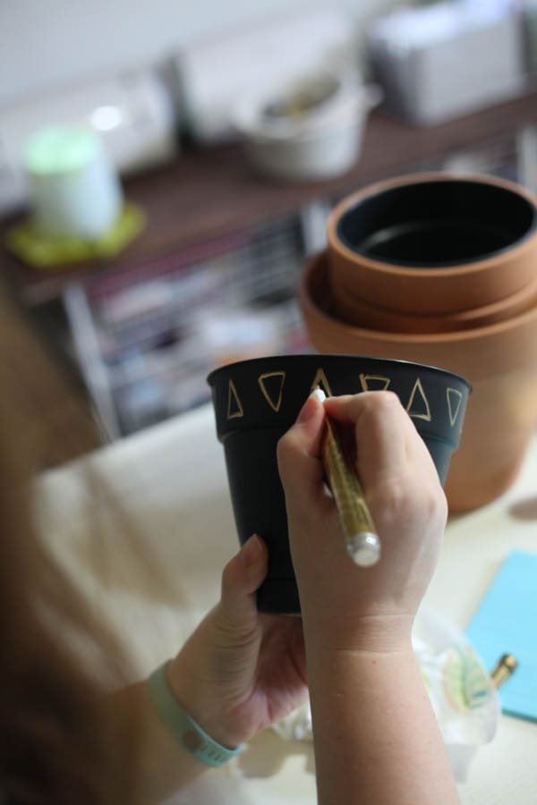 Alternating gold triangles being drawn onto a small black planter.