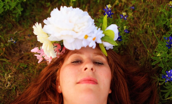 A woman laying in a field of Texas bluebonnets, wearing a homemade crown of flowers.