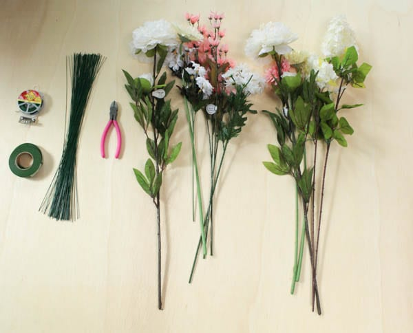 Piles of silk flowers on stems, next to wire cutters, floral wire and floral tape.
