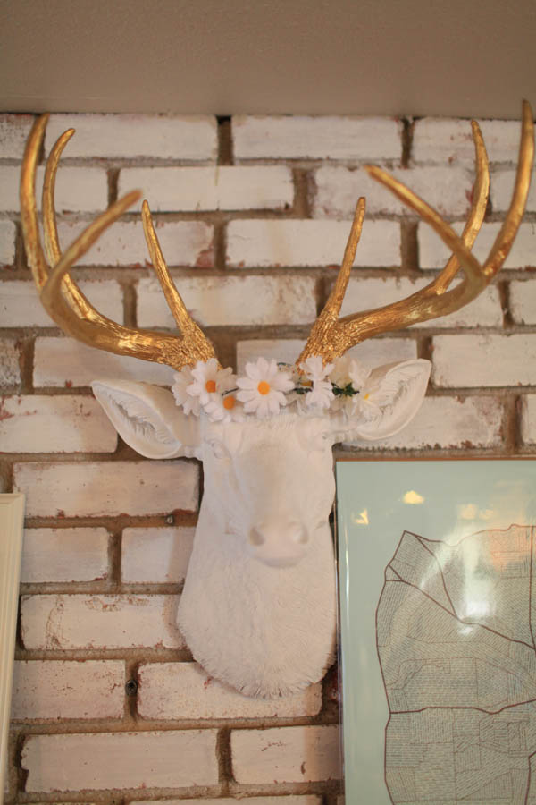 White and gold faux animal head decor mounted on brick, with a DIY flower crown on top of it's head.