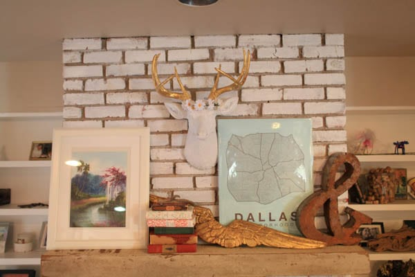 A mantle with various decor and a faux deer bust mounted on brick, wearing a faux flower crown.
