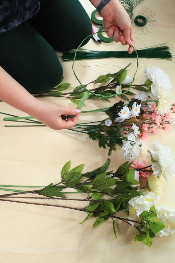 Floral tape being wound around a wire crown.