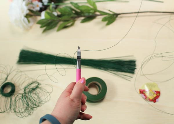 Cutting floral wire from a spool using pink wire cutters.