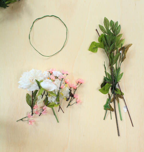 The elements of a homemade flower crown including a wire crown and silk flowers with the long stems cut down.