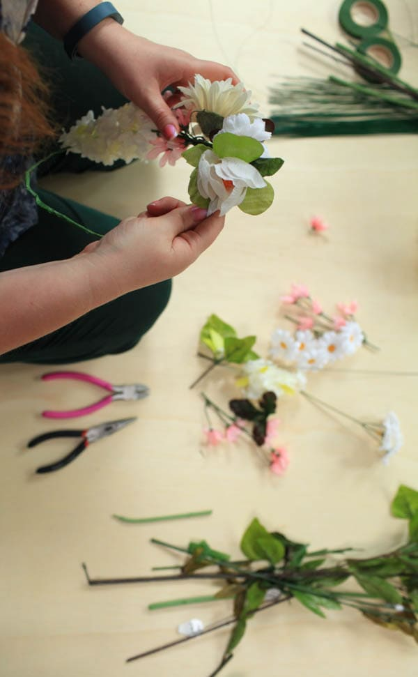 Flowers being attached to a wire crown.