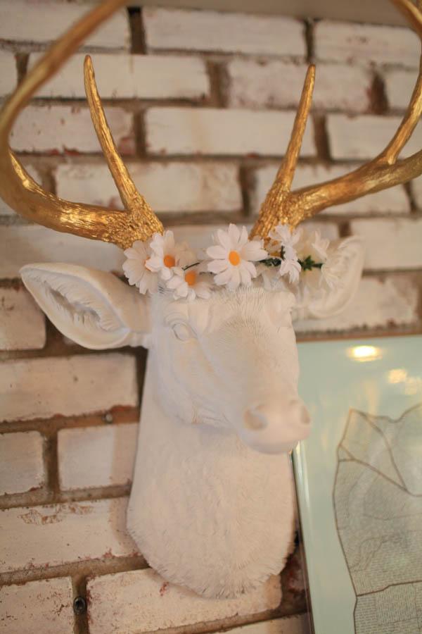 Close up of homemade silk flower crown on deer head decor.