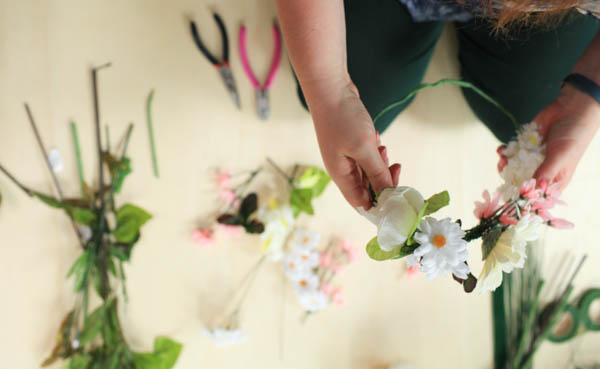 A DIY Flower Crown with Silk flowers and other supplies in the background.