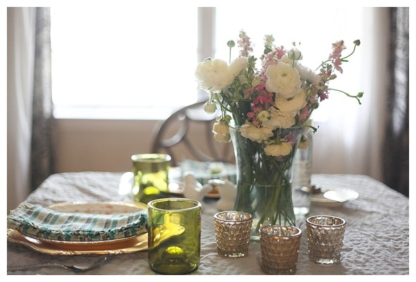 A kitchen table set with dishes and a vase of fresh flowers.