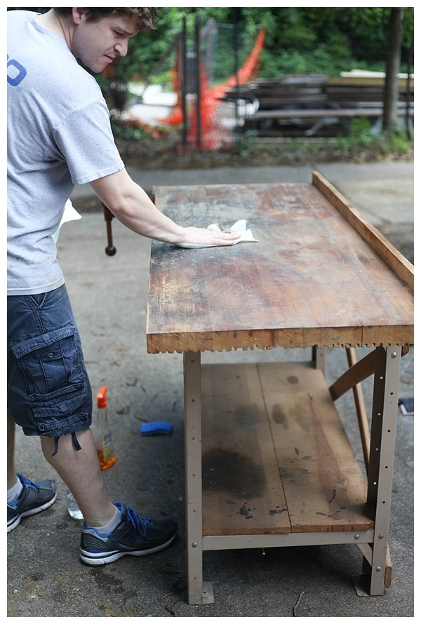 Cleaning the worktop of a vintage work bench.