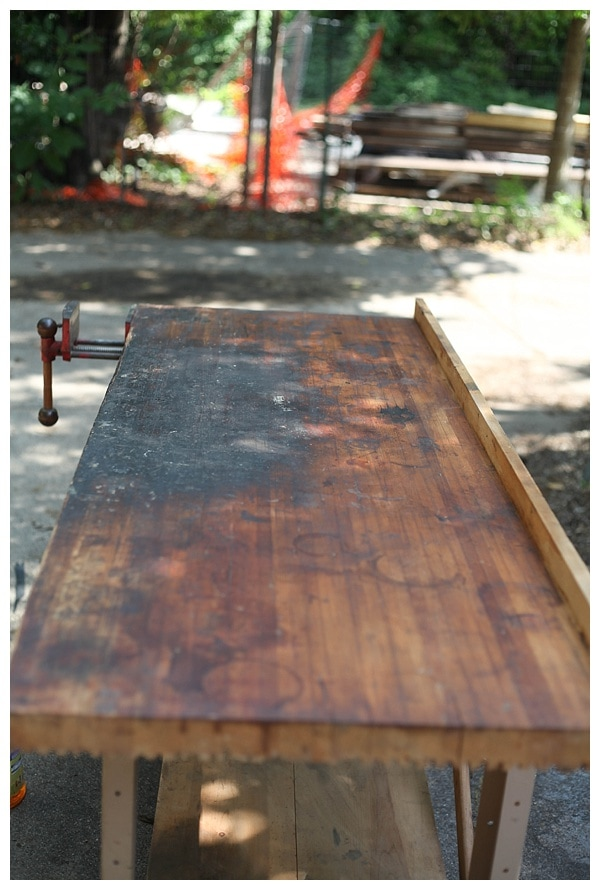 Dirty surface of vintage work bench, in the process of being sanded.