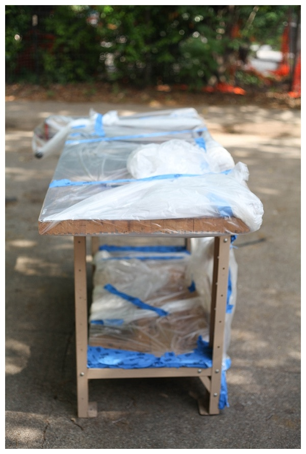Wooden workbench sitting in a driveway, with plastic coverings to protect wood from paint splatter.