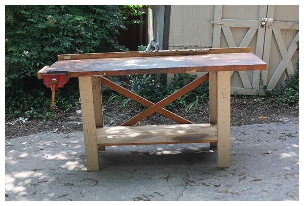 An old work table next to a wooden shed.