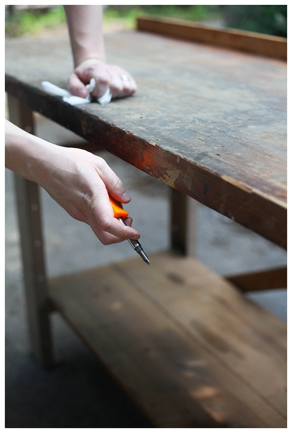 A man holding an orange screw driver next to an old wooden workbench.