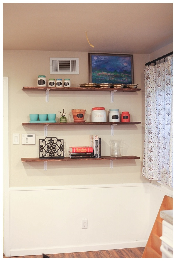 Kitchen wall with shelving above and an open space below.