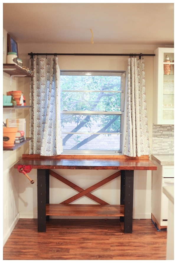 Vintage work table fit snug between  kitchen cabinets and wall.