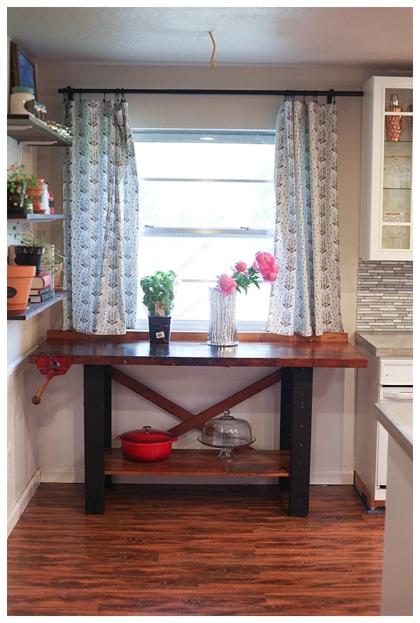 Flower pots, dutch oven and cake stand atop sanded and painted vintage work bench.