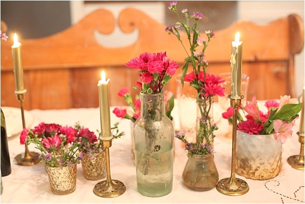 I love this table decor! I really like the idea of having multiple little containers of flowers spread out rather than one big one. I'm going to be keeping an eye out for cool bottles to use like this too! Super cute for Valentine's Day or any other day really!
