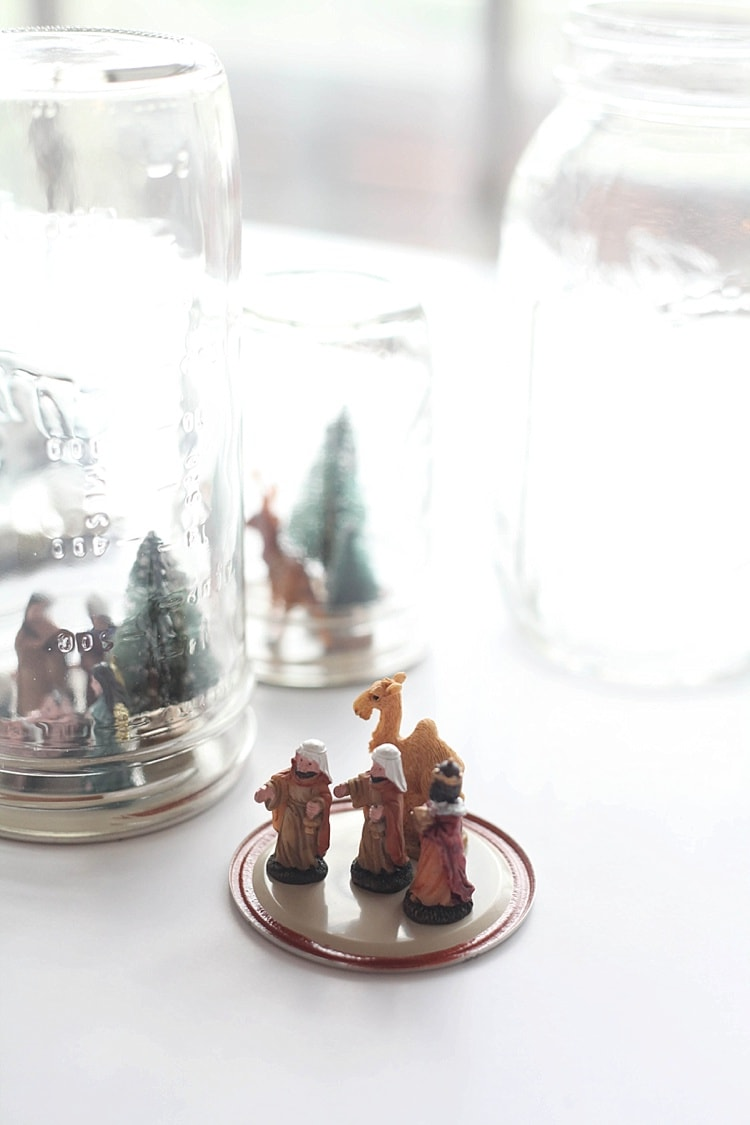 Mason Jars with Christmas settings glued to mason jar lid - How to make a snow globe in a mason jar
