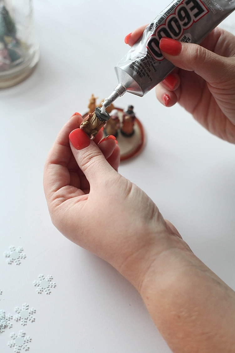 Close up of gluing small figurine for mason jar lid- How to make a snow globe in a mason jar