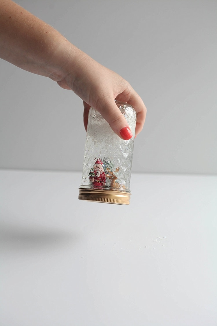 Completed homemade snow globe- Christmas figurines in a gold painted mason jar
