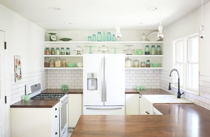 A white refrigerator with white cabinets