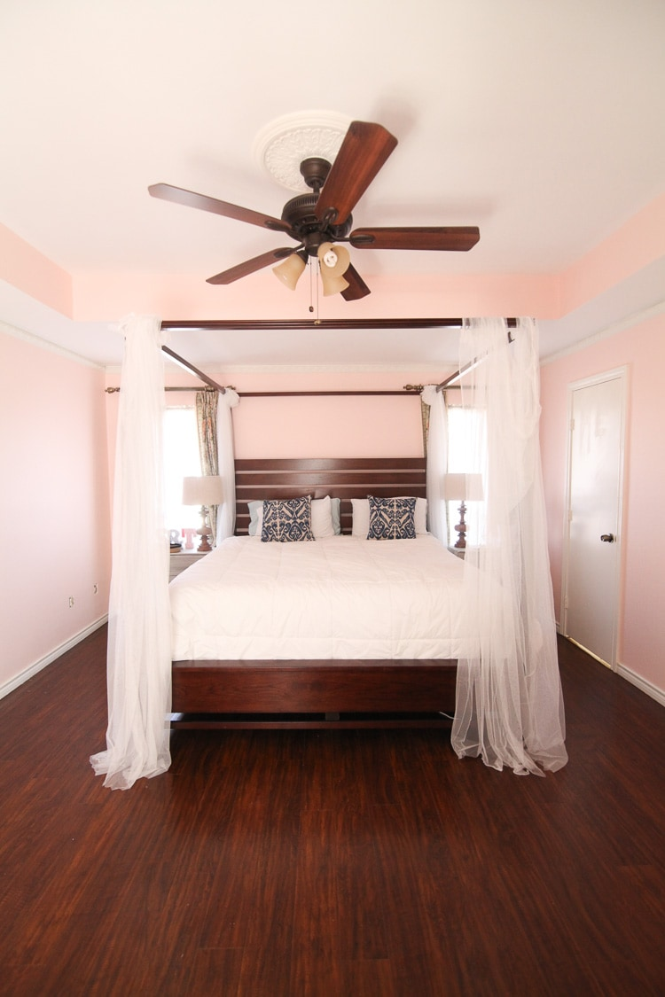 A large bed with white linens in a master bedroom with light pink walls.